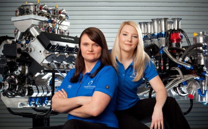 Student portraits in front of engine