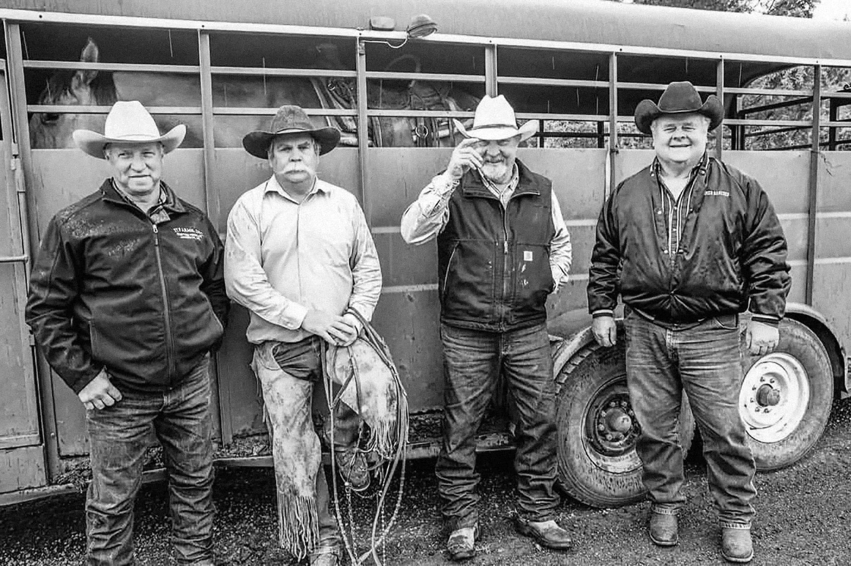 Four ranchers pose for camera against horse trailer; Mehrten Homer pictured to right