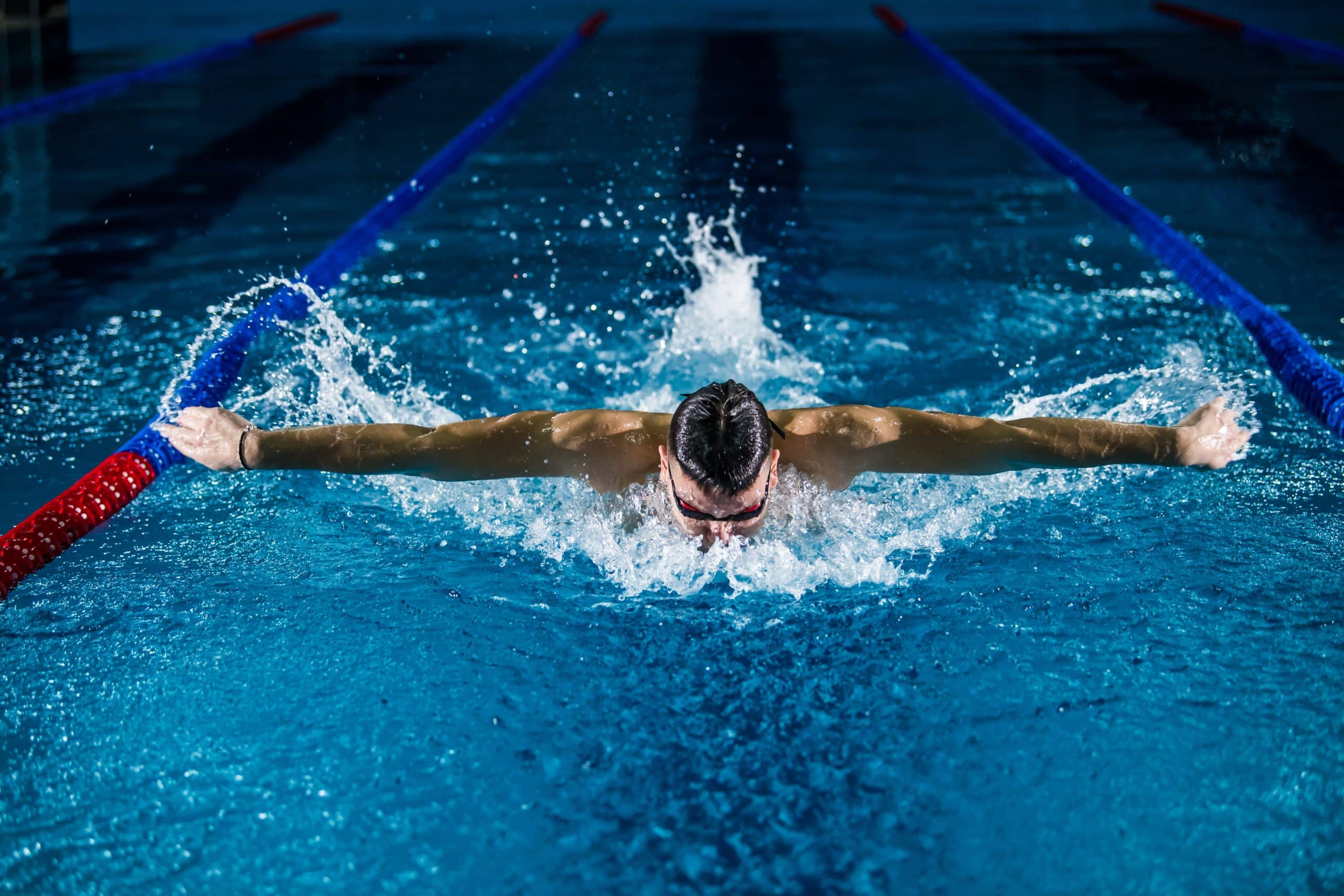 professional swimmer mid stroke in pool