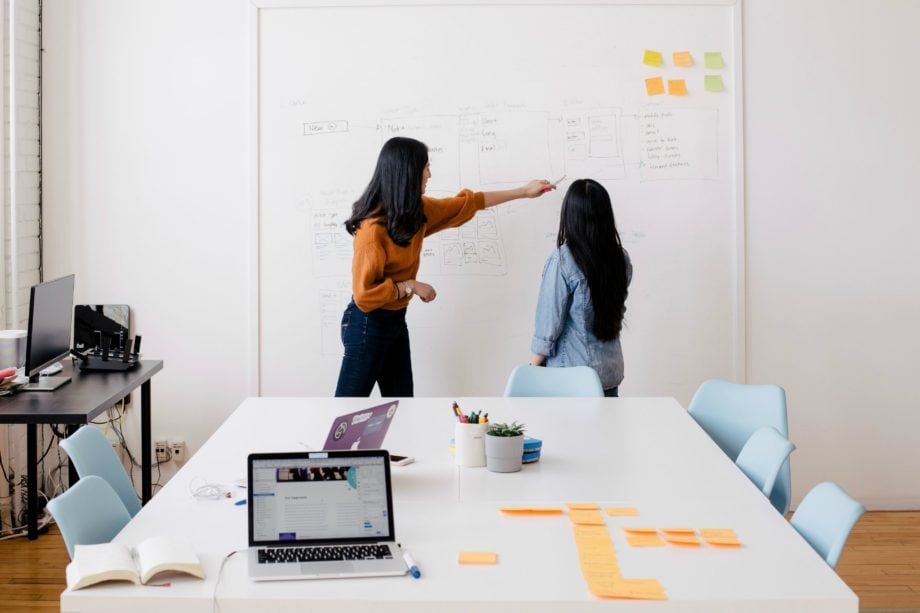 Two women doing work on a white board